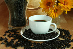Black coffee. Cup of black coffee and beans. Composition with flowers Stock Images