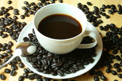 Black coffee. A white cup of black coffee surrounded by whole beans Stock Photography