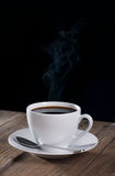 Black coffee. And textured wood against black background Stock Images