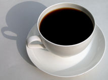 Black coffee. In a white cup and its shadow Stock Photo