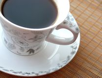 Black coffee. Cup of black coffee on bamboo mat royalty free stock photo