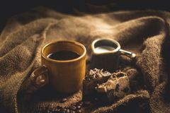 Black coffee Arabica In brown glass And milk and dessert Sack background in low light area Royalty Free Stock Images