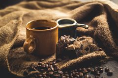 Black coffee Arabica In brown glass And milk and dessert Sack background in low light area Royalty Free Stock Photography