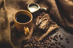 Black coffee Arabica In brown glass And milk and dessert Sack background in low light area Stock Photo