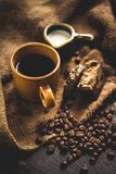 Black coffee Arabica In brown glass And milk and dessert Sack background in low light area Stock Image
