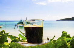 Black coffee on the beach Royalty Free Stock Photos