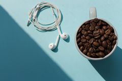 Black coffee beans in blue cup and white headphones on blue background with sunlight shadow top view. Morning drink concept. Cafe and breakfast background Stock Images