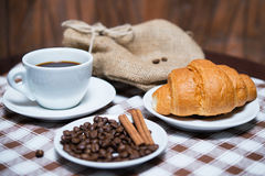 Black coffee with beans and croissant on tablecloth. Cup of black coffee with beans and croissant on tablecloth Stock Photo