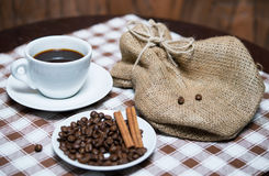 Black coffee with beans and sack on the tablecloth. Cup of black coffee with beans and sack on the tablecloth Stock Image