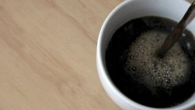 Black coffee being poured into white cup from above. stock video footage