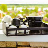 Black coffee in black cup from coffee machine with capsules onwooden tray on window with beautiful nature. Village background stock photography