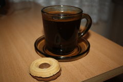 Black coffee in a black glassy cup with biscuit. For dessert on the brown table royalty free stock photography