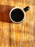 Black coffee in black and white ceramic cup. On the vintage wooden table with sunlight in the morning, Relaxing morning coffee.top view and copy space Stock Photo