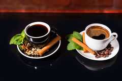 Black Coffee in Black and White Cups with Spices. High Angle View of Black Coffee Served in Black and White Contrasting Cups with Saucers Garnished with Cinnamon Stock Photo