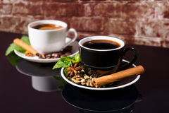 Black Coffee in Black and White Cups with Spices. Still Life Close Up of Black Coffee Served in Black and White Contrasting Cups with Saucers Garnished with Royalty Free Stock Photos