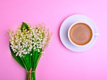 Black coffee and a blooming bouquet of lilies of the valley o Royalty Free Stock Photo