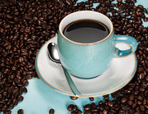 Black Coffee. In a blue cup amongst fresh unground beans royalty free stock photo