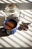 Black coffee in blue cup on white table with shadows from the blinds Royalty Free Stock Image