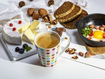 Black coffee with brown foam in a white ceramic mug. In colorful polka-dot, behind a round camembert cheese and a black frying pan with a fried egg, breakfast Stock Photography