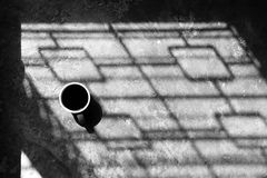 Black coffee on cement floor in morning light and shadow Royalty Free Stock Photo