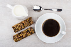 Black coffee, cereal bars and jug of milk on table. Black coffee, cereal bars and jug of milk on wooden table. Top view Royalty Free Stock Photography