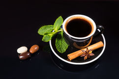 Black Coffee with Chocolate Covered Coffee Beans. Black Cup and Saucer with Strong Black Coffee Served with Fresh Spices - Mint Sprig, Cinnamon Stick and Star Royalty Free Stock Photography