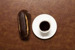 Black coffee, chocolate Eclair, coffee in white Cup, white saucer, on brown table, Eclair on stand stock images
