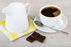 Black coffee, chocolate and jug of milk on napkin. Black coffee, chocolate and jug of milk on yellow napkin stock photo