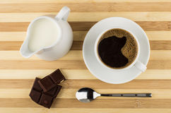Black coffee, chocolate and jug of milk on striped table. Top view Stock Photography