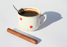 Black coffee with cigar. White cup with red dots full of black coffee with spoon and cigar aside royalty free stock photo