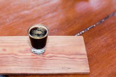 Black coffee in clear glass is placed on a wooden table. Black coffee in clear glass is placed on a wooden table in the coffee shop Stock Image
