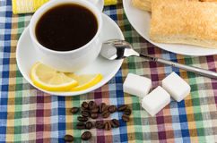 Black coffee and coffee beans, sugar and flaky biscuits Stock Photos