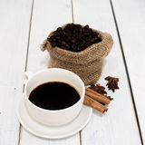 Black coffee in coffee cup and beans with cinnamon sticks on the Stock Image