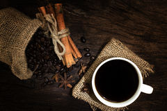 Black coffee in coffee cup and beans with cinnamon sticks on the Stock Photos