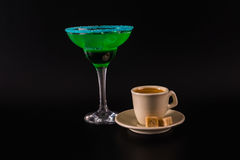 Black coffee and colorful drink in a cocktail glass, with ice cu Stock Photos