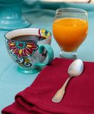 Black coffee in a colorful flower print cup with orange juice Stock Images