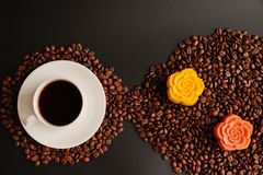 Coffee and colorful Chinese mooncakes on the coffee beans with black background. View of a cup of black coffee and colorful Chinese mooncakes on the coffee beans royalty free stock images