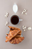 Black coffee, cream, fresh croissants and toast on a light beige Royalty Free Stock Image