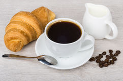 Black coffee, croissant, milk jug and coffee beans on table. Black coffee, croissant, milk jug and coffee beans on wooden table Royalty Free Stock Photos