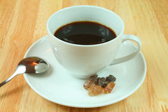 Black coffee in a cup. A cup of black coffee with brown sugar in white porcelain Stock Images