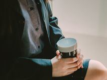Black coffee cup in asian business woman hand 30s to 40s hold. And sit with black shirt and skirt from coffee break time with soft focus background Royalty Free Stock Images