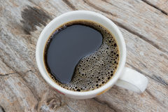 Black coffee. Coffee cup and coffee beans on wooden table Royalty Free Stock Photo