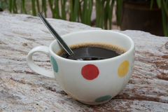 Black coffee. Coffee cup and coffee beans on wooden table Royalty Free Stock Photography