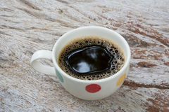 Black coffee. Coffee cup and coffee beans on wooden table Royalty Free Stock Images