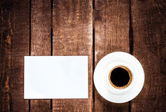 Black  Coffee cup and blank business card on wooden table. White Stock Photos