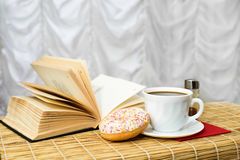 Black coffee in a cup with cinnamon, donut and open book. On the mat Stock Photos