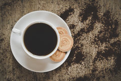 Black coffee cup with cookies on vintage wooden table. Top view. Black coffee cup with cookieson vintage wooden table. Top view stock photo