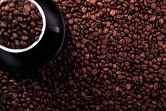Black coffee cup with dark roasted beans background Royalty Free Stock Photo