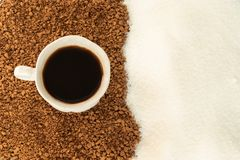 Black coffee in a Cup with entourage of ground coffee and sugar. The view from the top stock photo