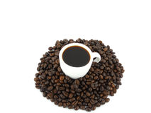 Black Coffee. In a cup on a heap of coffee beans Stock Images